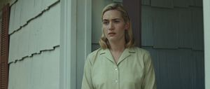 "Movie still from ""Revolutionary Road"" of Actor Kate Winslet being lit by soft lighting outside of a house. The lighting is meant to emulate sun around dusk."